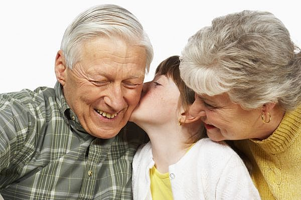 child kissing grandparents