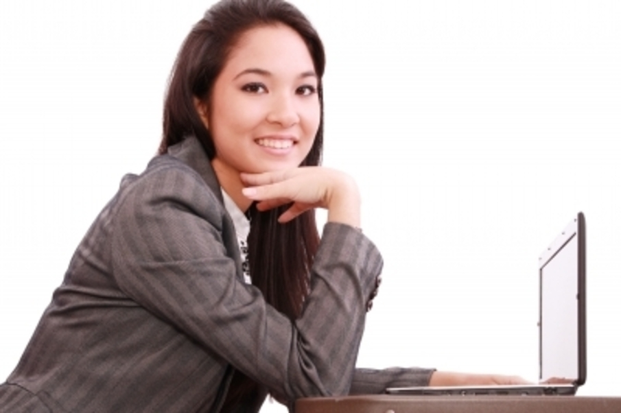 woman dressed in a casual suit sits in front of an open laptop