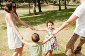 Family of four holding hands in a park