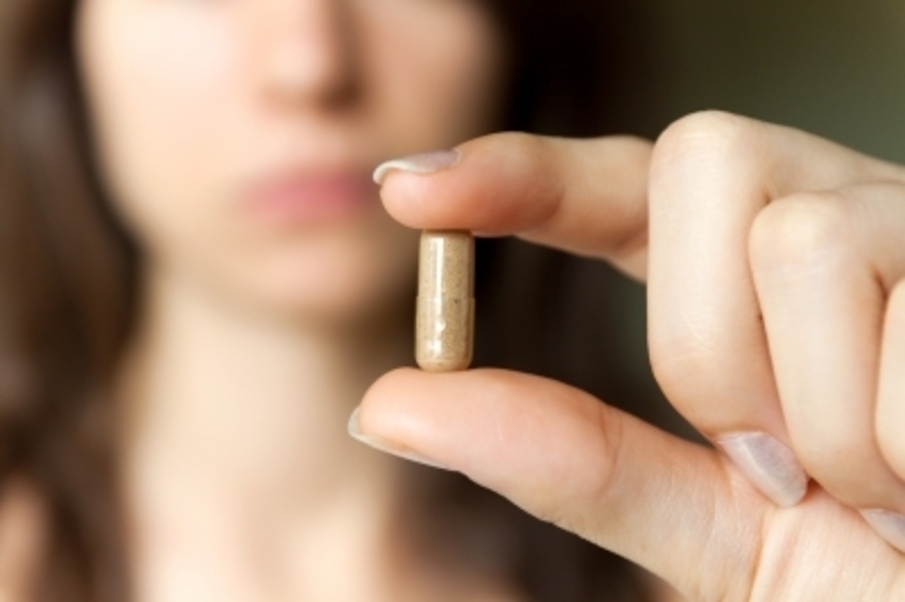 blurry woman holding a pill