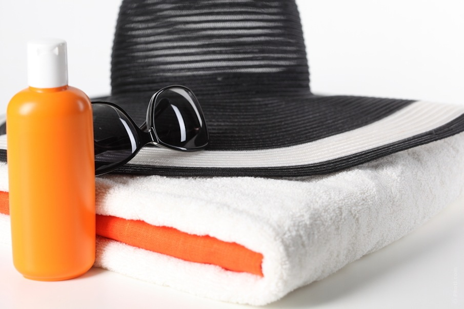 hat, sunglasses and towel, sunscreen lotion
