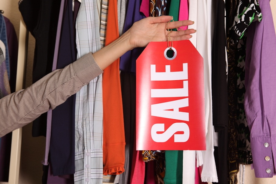 clothes in a closet and a hand holding up a sale sign