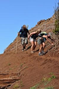 a group of three hiking down a desert hil