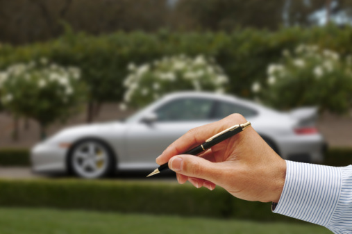person holding a pen with car in the background