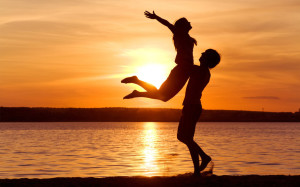 girl jumping in the guy's arms by the sunset