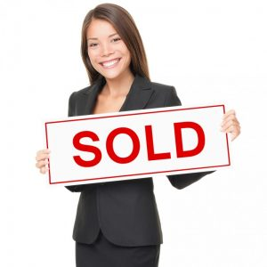 woman holding a sold sign for successful Real Estate Agent