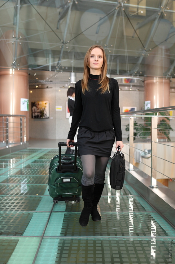 woman walking through an airport with luggage