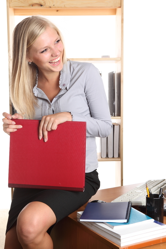 woman sitting on a desk holding a red folder