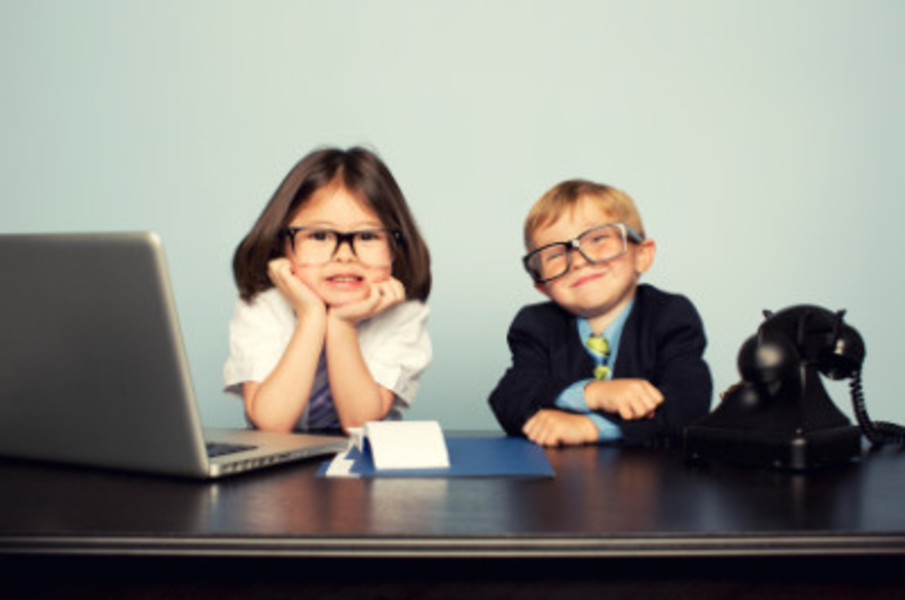 boy and girl with glasses and in business attire at a desk with a laptop and phone