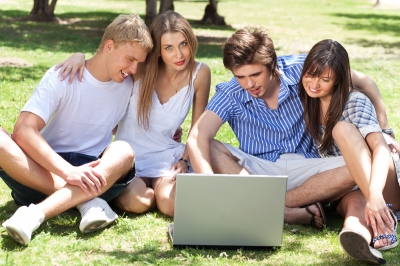 two men and two women on a lawn studying with a laptop