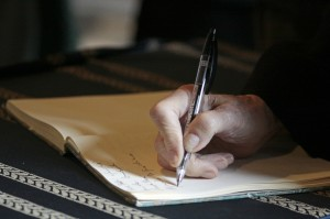 a person writing on a legal pad with a pen to study