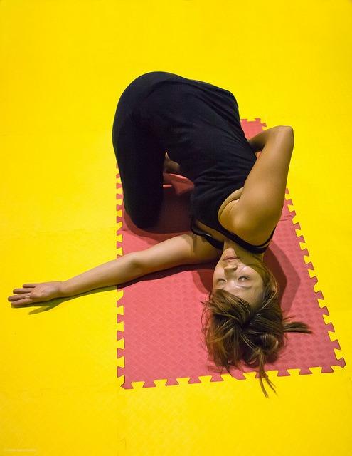 girl doing yoga on a pink and yellow mat