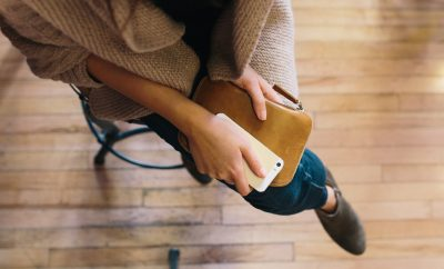 girl with wallet and cell phone sitting cross legged
