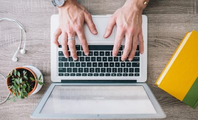 woman with good quality of life at work typing on laptop