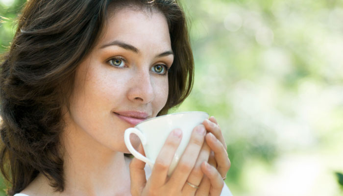 woman drinking cup of green tea