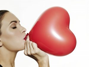Girl blowing up a red heart shaped balloon