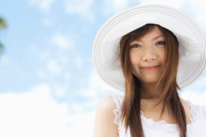 Young woman smiling wearing white sunhat during summer