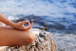 girl meditating on beach rock to relieve stress and help her gut