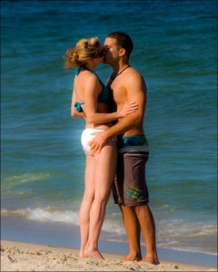 Couple kissing on beach for anniversary