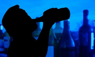man drinking alcohol out of bottle