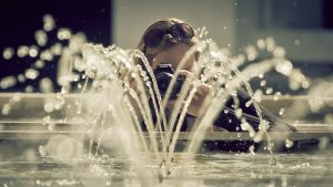 woman in front of a fountain taking photo