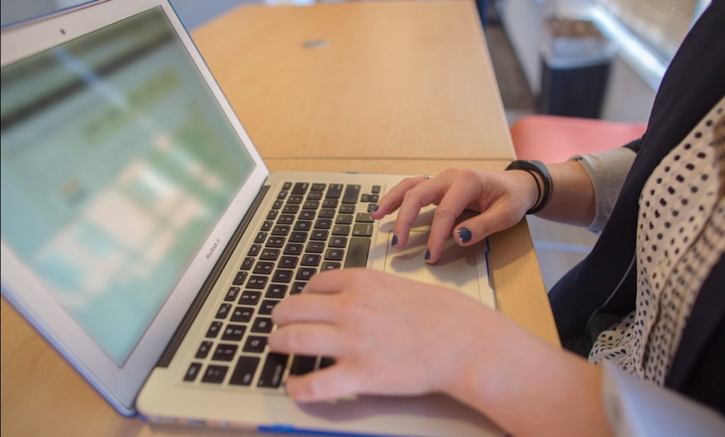 woman working on laptop for miss millennia internship and full-time job