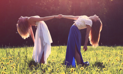 two friends holding hands in a meadow