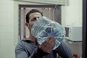 man drinking a lot of water to recover from 5k