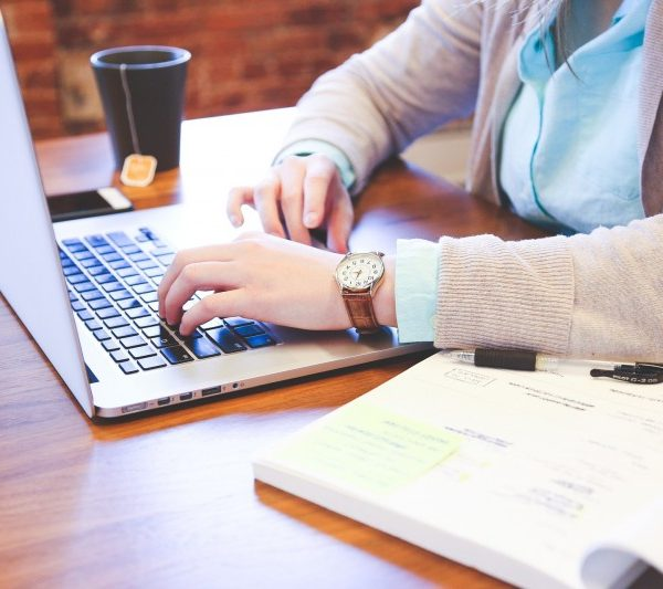 woman At desk with coffee hoping to get promoted