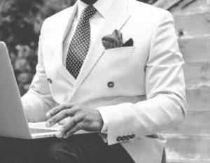 man sitting at computer managing successful stock portfolio