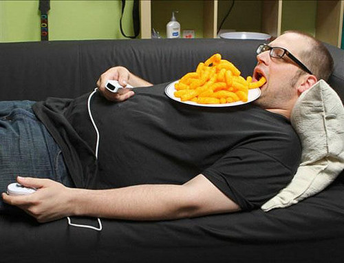person laying on couch eating cheetos