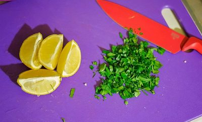sliced lemon and chopped parsley on cutting board with knife showing cooking skills