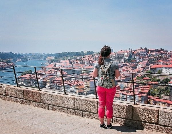 girl standing with back to camera looking out over city thinking about why to travel when you're young