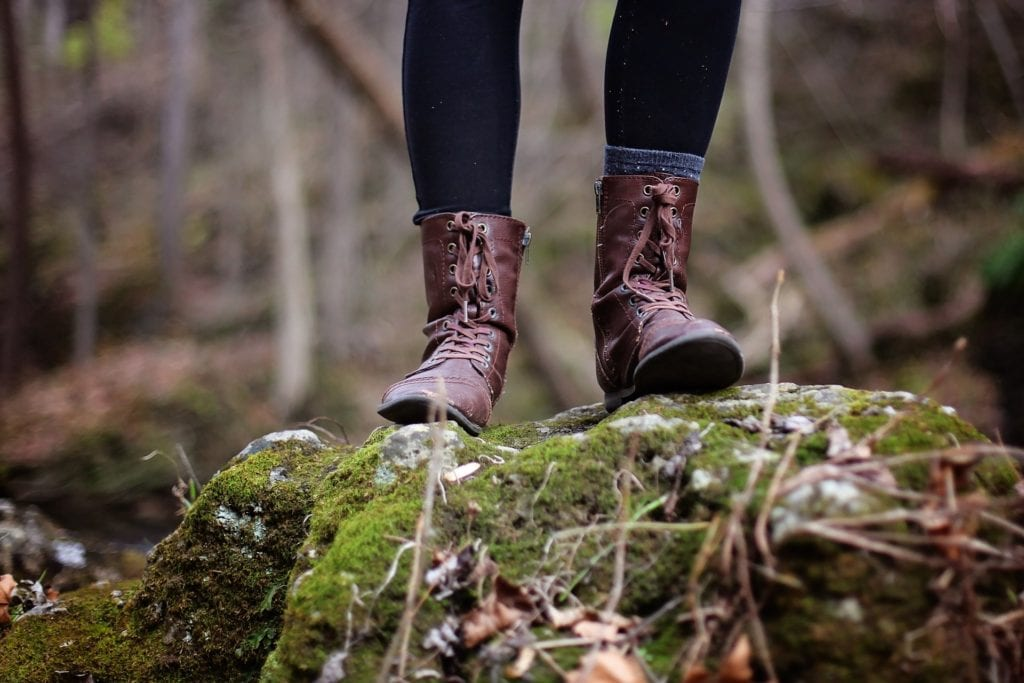 Girl's feet standing on mossy rock