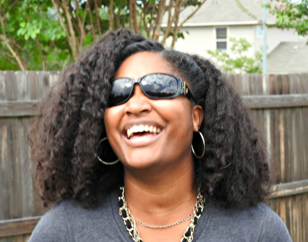 Jasmine Watts laughing with her sunglasses on