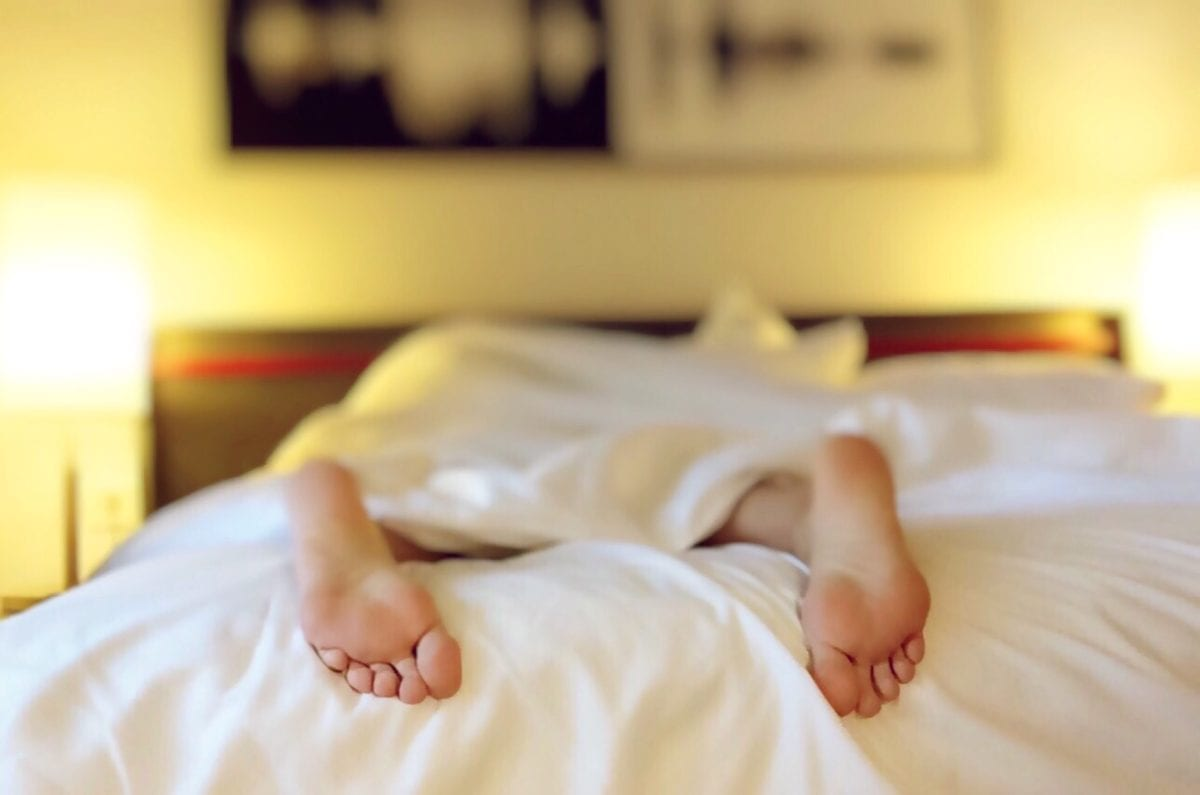 feet of someone sleeping in bed