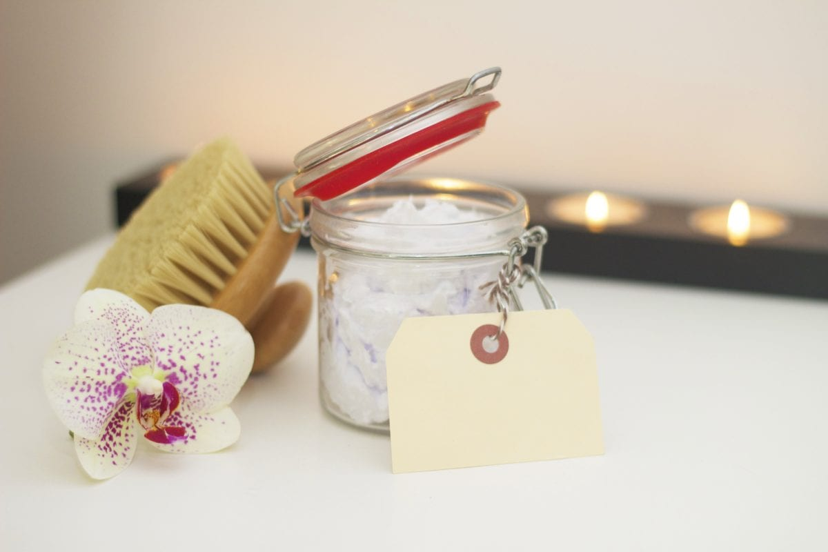 candle, brush, and flower with a jar of cream