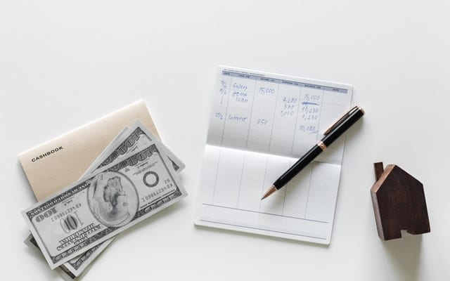 checkbook with pen and cash on white table
