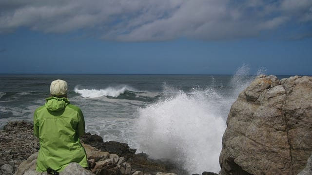 person sitting on rock looking at ocean