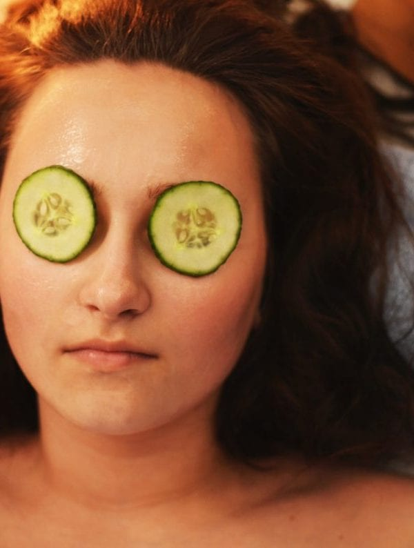 woman with cucumbers on her eyes