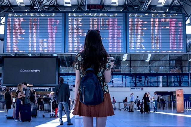 girl standing in airport with backpack