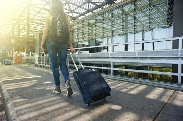 woman pulling rolling suitcase through airport