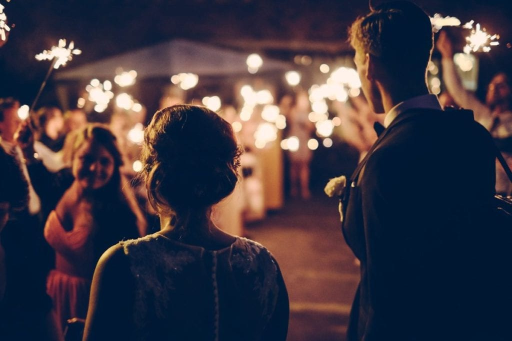two people at their wedding with sparklers in the background
