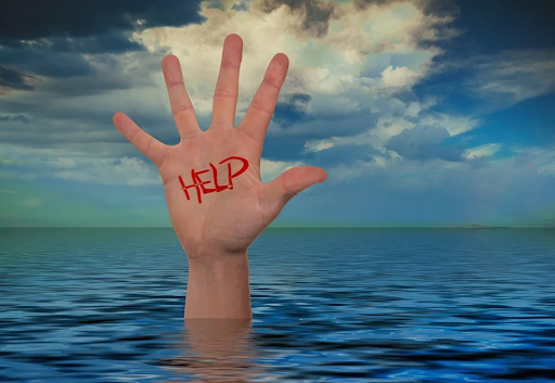 "person's hand reaching out of water with ""Help"" written on it"