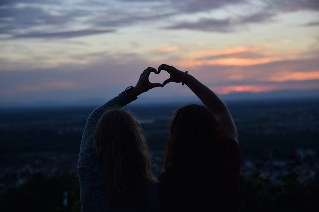 two people outside making a heart with their hands