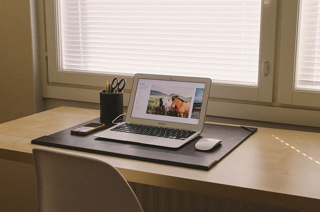 laptop, mouse, phone, and scissors at desk in front of window