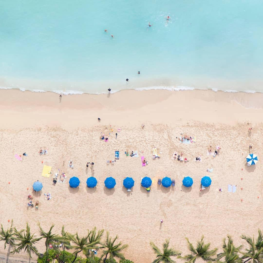 birdseye view of beach with blue umbrellas and people