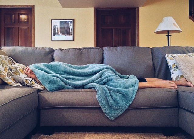 person lying on couch under blanket