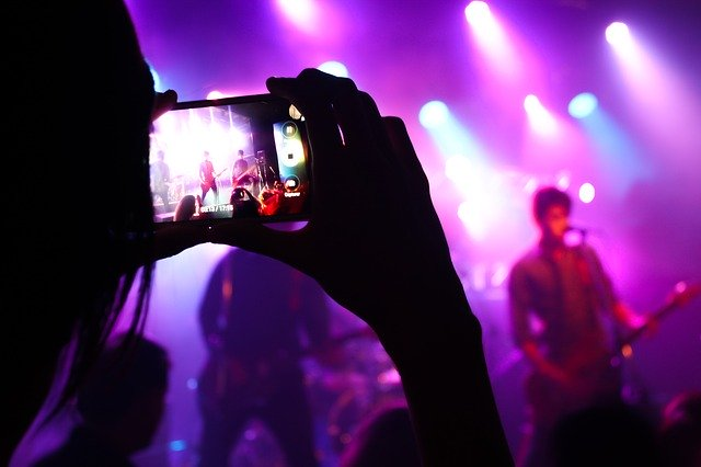 person taking a picture of a concert