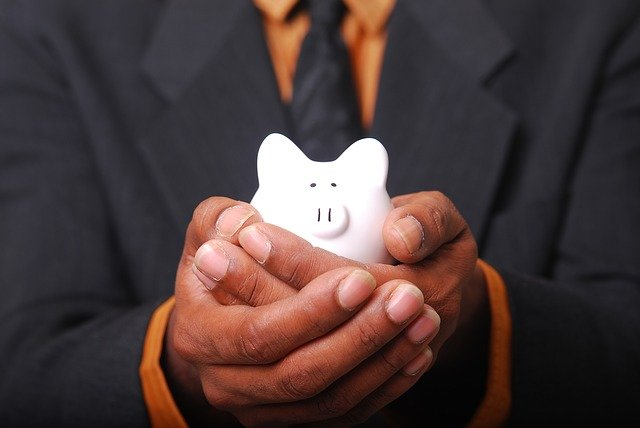 person in a suit holding a small piggy bank